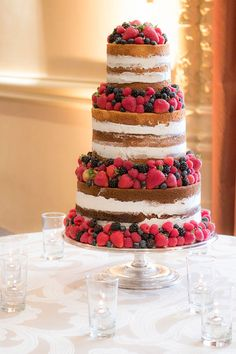 A Naked Cake Adorned with Summer Berries on @Nvlinens Ankara Taupe linens for a neutral, chic cake table