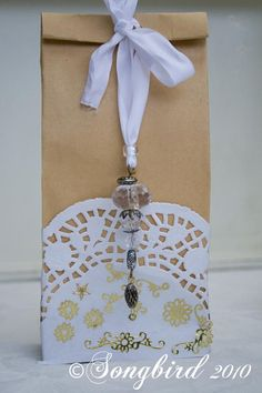 Wrapping - Brown paper bag with a white paper doily glued onto the bottom. Add an inexpensive Christmas ornament to the top to tie.