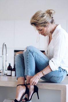 Le Fashion Blog Effortless Look Camilla Pihl Low Messy Bun White Button Down Top Stack Of Gold Bracelets Distressed Raw Hem Skinny Denim Black Ankle Strap High Heeled Sandals Via Camille Pihl Photo by lefashion | Photobucket