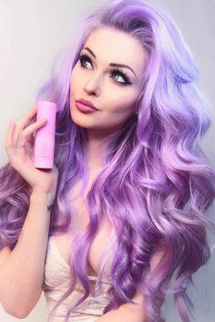 Barbie-Look - lange lockige Haare, gefärbt in verschieden Nuancen von Lila, Ansatz mit blauer Farbschttierung, lila Längen mit hellrosa Reflexen, Katzenaugen mit schwarzem Lidstrich schminken, dicke Lippen mit rosa Lippenstift, dichte dünngezupfte Augenbrauen