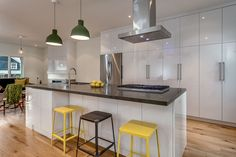 High gloss cabinetry with Muuto Unfold pendants and great CB2 counter stools