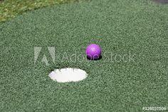 Purple golf ball beside hole on putt putt or miniature golf course