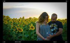 Fotografia annuncio gravidanza - futuri genitori in un campo di girasoli.