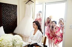 Love this getting ready photo with the bridesmaids peeking through the window!