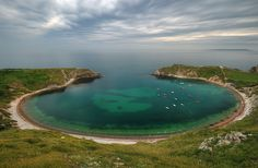 One of the finest icons of the British coastline, Lulworth Cove is a natural land formation in Dorset; England on the Jurassic Coast.