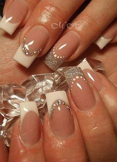 Fill your nails with this wonderful ensemble of glitters and beads! This French manicure starts off with a clear base coat and lined with thick white coating and silver glitter for the tips. Beads are added to further accentuate the nail design.