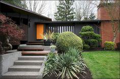 midcentury modern exterior paint - very dark grey and orange door. House Paint Exterior, Exterior Paint Colors, Exterior House Colors, Paint Colors For Home, Exterior Stairs, Paint Colours, Mid Century Ranch, Mid Century House, Modern Exterior