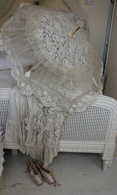 I love white lacy old clothes and parasols. These are pretty tattered and dirty so I am sure they have a wonderful story to tell. If only clothes could talk. This is too beautiful. :-)