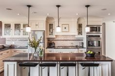 Pendant Lighting Over Kitchen Island | Dazzling pendant lights above a white kitchen island with dark granite ...