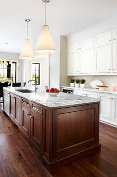 White outer cabinets with wood island, white countertops, white backsplash