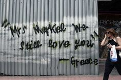 A woman walks past a slogan reading 'Mrs Merkel -we still love you-Greece' on a sheet metal covering a burned down building in Athens on June 10, 2015. (LOUISA GOULIAMAKI/AFP/Getty Images) | Athens' Badass Street Art