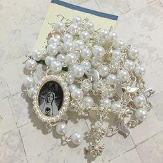 Terço confeccionado com perolas brancas de vidro 8m/m, banho prata,crucifixo com mini pérolas brancas,entremeio resinado Fátima preto e branco com mini perolas.entremeios entre o Pai Nosso pássaros. <br>Como usar o terço de noiva: <br>- O terço pode ser enrolado no punho da noiva, deixando cerca de 10 cm soltos, quando o terço e o bouquet forem pequenos; <br>- Pode ser colocado sobre as flores do bouquet; <br>- Envolvido no caule das flores que compõem o bouquet ( super recomendo esse)…