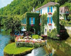 In the heart of the picturesque village of Brantôme, France, is the pretty hotel Moulin de l'Abbaye with bright blue window shutters, pink flowers and covered in green ivy.     ᘡղbᘠ