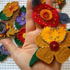 felt flowers - make into pins to embellish sweaters