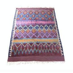 A gorgeous, large vintage jewel-tone Moroccan rug from Anthropologie, named the Agadir Twists Rug. The extremely comfortable, plush rug features a beautiful, diamond pattern with vibrant colors and light tassels on each end. This would be perfect for a modern, midcentury, eclectic styled home.