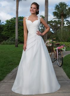 An illusion and beaded lace Queen Anne neckline adorns this asymmetrical A-line organza gown. An illusion keyhole back completes this sweet look. https://www.sweetheartgowns.com/sweetheart/6125