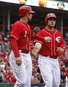 Cincinnati Reds' Zack Cozart (2) congratulates teammate Joey Votto (19) at home plate after they scored on a Jay Bruce double hit off Houston Astros starting pitcher Lucas Harrell during the third inning of a baseball game on Saturday, April 28, 2012, in Cincinnati.
