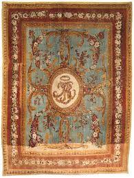 TAPIS D'AUBUSSON D'EPOQUE LOUIS XVI  En haute laine, de forme rectangulaire, le centre orné d'un médaillon à fond ivoire présentant le monogramme BR sur un fond bleu ciel orné de rinceaux d'acanthe entrelacés, bordure rouge à guirlande de fleurs et tore d'acanthe  442 x 328 cm. (174 x 129 in.)  A LOUIS XVI AUBUSSON CARPET