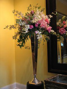 Rose and orchid arrangement on silver pedestal