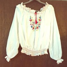 "Vintage off-shoulder peasant blouse Vintage off-shoulder peasant blouse, this is an authentic Hungarian hand-embroidered peasant blouse (my mother is from Hungary and my grandmother would send these occasionally over the years). 1970's. It can be worn on or off the shoulder. Stitch embellished ruffles decorate the sleeve ends, neck and bottom openings. There is no tag, (these are hand made)but it can fit a variety of sizes 22"" long, 42"" chest (billowy style) 26"" bottom elastic hem w…"