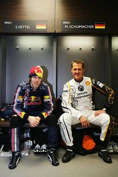 Former Formula One World Champion Michael Schumacher of Germany talks with fellow countryman Sebastian Vettel of Red Bull Racing in the changing...