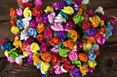 Dime-size Mini Paper Roses  Handmade by 5 old ladies in Mexico City.... and furthermore, Angela's mother got drafted to assort the colors once they hit state side! She's done thousands! These adorable roses are bright & beautiful and can be used for wrapping napkins, wedding decorations, cards, cello bags, sugar skulls or decorating something special. Assorted colors-wire stems. A bunch is 12 roses.   Colors - We now have only bright colors available. The brights include red, bougainvillea…