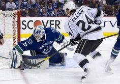 Goalie Cory Schneider #35 of the Vancouver Canucks stops Colin Fraser #24 of the Los Angeles Kings