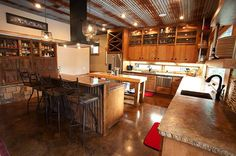 Modern rustic kitchen with concrete counter-tops, stained concrete floor, and a ceiling of rusting corrugated metal. Design Jobs, Home Design, Design Ideas, Floor Design, Concrete Kitchen, Concrete Floors, Stained Concrete Countertops, Kitchen Flooring, Barn Tin
