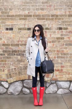 Rachel Parcell is wearing a khaki trenchcoat, classic denim button-up shirt, black leggings, bright red Hunter boots and carrying a studded black leather purse. Trench: Burberry, Shirt: J.Crew, Leggings: Lululemon, Boots: Hunter, Bag: Valentino, Glasses: Prada