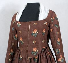 1790s gown, fabric >20 years older. Glazed cotton. Extra fabric may have been removed from the skirt to create the more au courant long sleeves. The bodice and sleeves are lined with beige linen. The bodice front opening has an under extension of later roller print cotton, probably added when the dress was remodeled. The dress is completely hand sewn but with several different types of thread. (Vintage Textile)