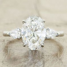 Brilliant pear-shaped diamond surround the oval-cut diamond in this engagement ring by Ken and Dana Designs.