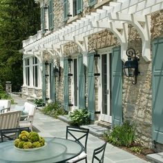 small white pergola attached to stone house with light blue shutters and outdoor glass table and chairs on slate bluestone patio Exterior Color Schemes, Design Exterior, Exterior House Colors, Exterior Paint, Exterior Shutters, Stone Exterior, Exterior Shutter Colors, Stone Facade, Custom Home Builders