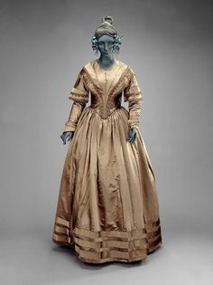 Woman's dress in four parts (dress)  American, 1835–40   Woman's dress (a), alternate bodice (b), shouder cape (c), and bow (d). Brown satin timmed with piping, bands, bows, and pleating of same brown satin. Attached bodice trimmed with soutache braid fo same color. Cape trimmed with long brown fringe. Both bodices have long sleeves