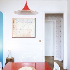 Bright dining space with a red pendant light, a red dining table, and a modern white chair
