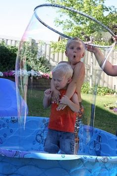 kiddie pool + hoola hoop + water + dish soap = bubbles big enough to swallow your kid