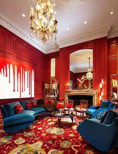 painting on the wall, shelving unit in gold. blue accent on red . rich colors and style
