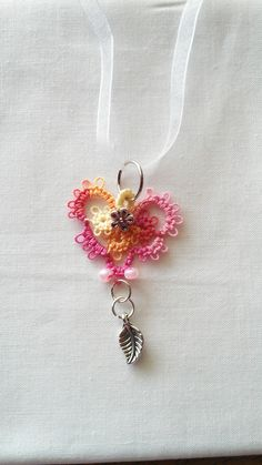 "Variegated coral/pink/yellow tatted lace pendant with pewter flower and leaf accents, pink seed beads. 18"" white chiffon ribbon. $10.00"