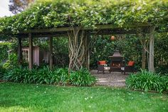Tuck a free standing fireplace and a couple of chairs in a cozy nook or under a trellis like this one away from the house.