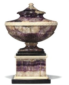 A GEORGE III BLUE-JOHN AND ALABASTER OVAL SOLID URN  CIRCA 1780  The gadrooned body with a band of Vitruvian scroll on a waisted socle and rectangular plinth bordered with black and white marble, finial and slate base replaced  15 in. (38 cm.) high; 10 in. (26 cm.) wide