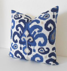One decorative pillow cover. Designer ikat fabric. Colors include royal, navy and tan on an ivory background. Backed with a coordinating solid ivory and finished with a concealed bottom zipper. Pattern placement may vary but will be always be centered and matching if you purchase more than one.  Available made to fit your choice of 16x16 or 18x18 size insert.  Pillow form not included. Also available in berry here: https://www.etsy.com/listing/170542024/berry-red-coral-ikat-decorative-pillow…