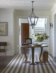 Center hall table and a breezy striped rug.
