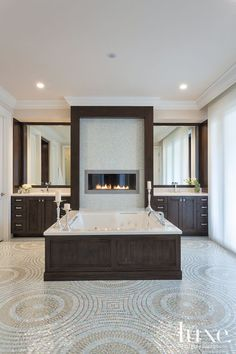 The spa like master bath spotlights an undermount tub from European Sink Outlet against a Heat & Glo Cosmo linear fireplace surrounded by Sicis glass mosaics from Rainbow Tile.