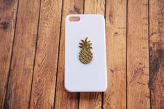 A hand-hammered 22kt gold plated pineapple pendant laid on our white hard shell case. Handmade to order!