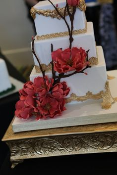 Absolutely gorgeous #weddingcake by Party Flavors from the #ORLPWGShow! The gold details & stunning red, sugary flowers are just perfect! Can't wait to see what they bring to the next Orlando PWG Wedding Show! #weddingcake  #wedding #gorgeouscake #elegantcake #moderncake