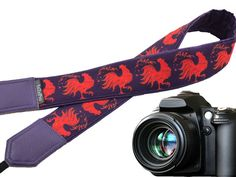 Rooster camera strap. Red and dark purple camera accessories. Symbol 2017. Stylized red cock. Padded camera strap. Photo accessories.