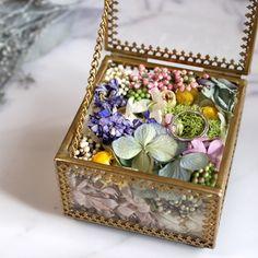 真鍮で縁取られたガラスのケースにドライフラワーとプリザーブドフワラーを詰めてアレンジしたガラスのリングピローです。