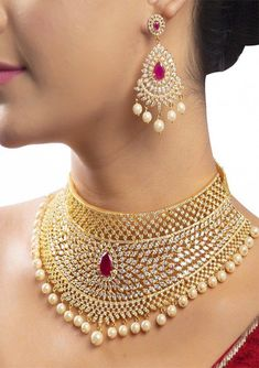 Leela Necklace A marvelous piece of gold finish grand choker necklace with an array of white stones, pearls and ruby, and a matching pair of magnificent ear studs with dangling pearls. This is aptly suitable for all grand occasions! Indian Jewelry Sets, Indian Wedding Jewelry, Bridal Jewelry Sets, Indian Bridal, Jewelry Design Earrings, Gold Jewellery Design, Necklace Designs, Diamond Jewellery, Jewelry Necklaces