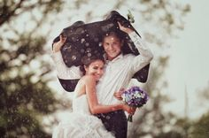 Couple sheltering under groom's jacket from rain