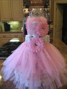 Tutu diaper cake with matching flower headband.  Just roll up 100 diapers with rubberbands, making 4 tiers and cover the 3rd tier with a baby tutu and top tier with a baby headband.  Makes a great centerpiece and a fun gift for the mom to be.