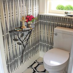 Kelley Flynn made a big statement in this small bathroom by covering the walls with pleated fabric and the floors with equally graphic tiles. She accessorized a floating shelf with flowers and curiosities to bring even more style to the space.